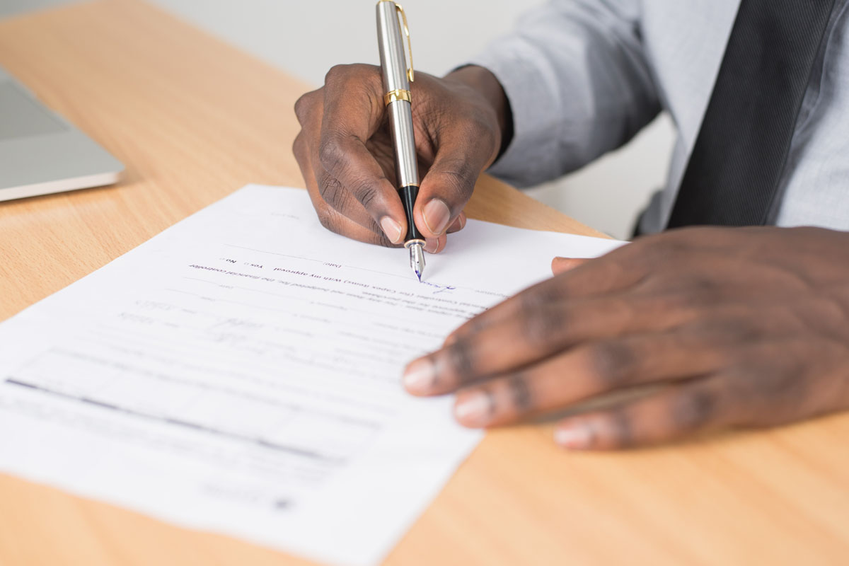 man signing a form