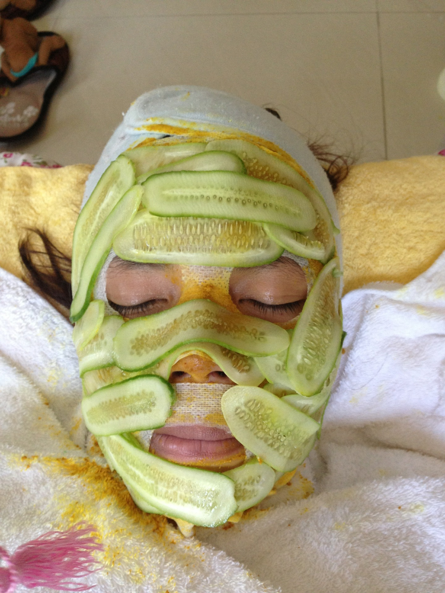 Woman draped in cucumber on her face