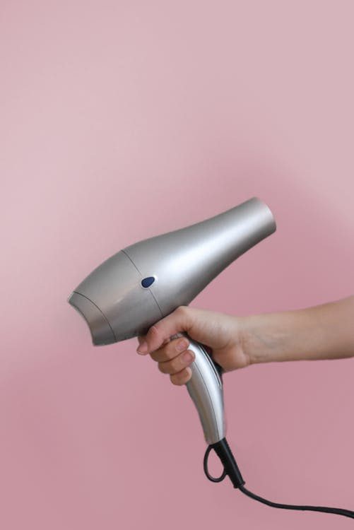 holding a hair dryer